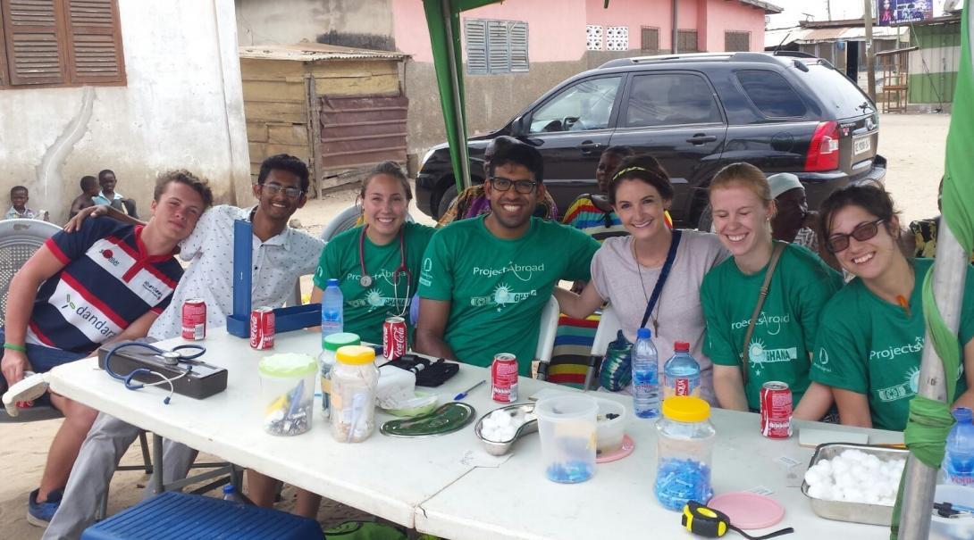 Als deel van hun groepsreis Public Health in Ghana, poseren de stagiaires voor een groepsfoto tijdens een pauze